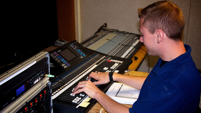 """SCT Sound Designer Darin Alsup programs and manages sophisticated electronic equipment in the sound booth. Individual body microphones for cast members controlled and mixed together from """"the booth."""""""