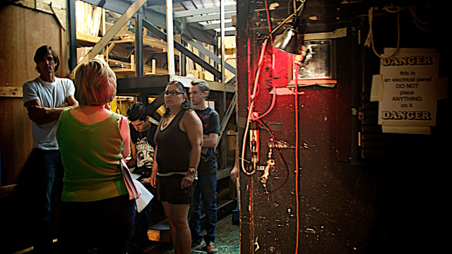 Scenic Designer Brian Johnson and Stage Manager Putsy Hong (with glasses) confer with Assistant Stage Manager and Properties Mistress Elaine Saculla (back to camera) while two stagehands listen.
